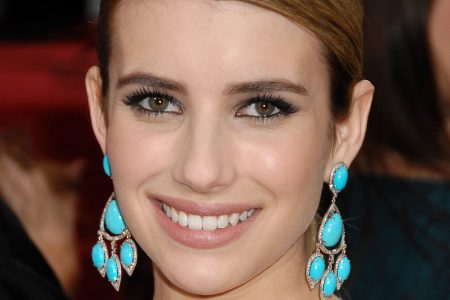 Emma Roberts smiles at a red carpet event. Her brown hair is slicked to the side and tied back. She wears dangling aqua coloured earrings.