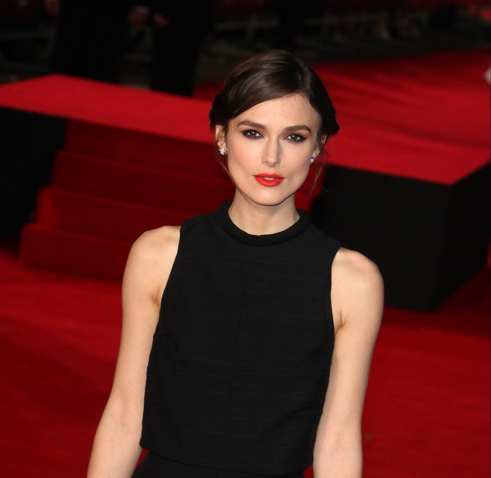 Keira Knightley attends a red carpet event. She wears a sleeveless black dress and bright red lipstick. Her hair is dark brown and tied back with a side part. She looks very elegant.