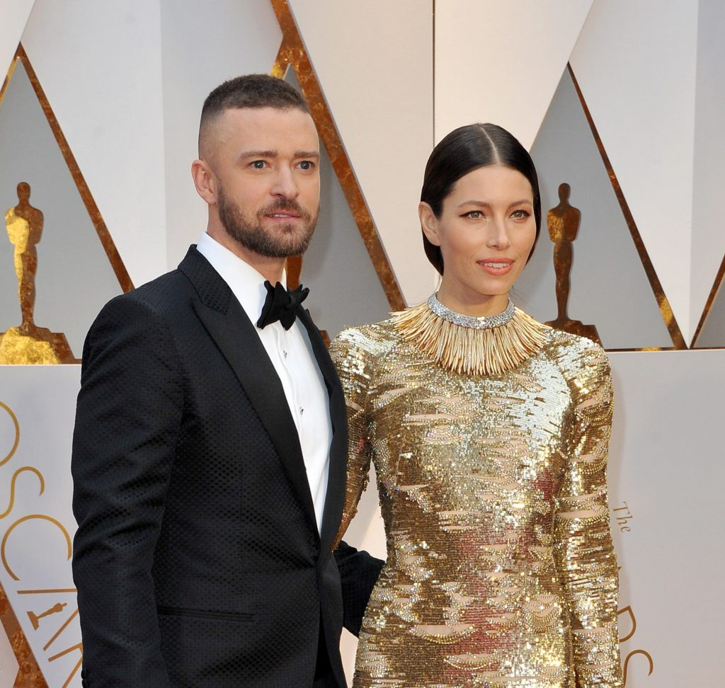 Justin Timberlake and Jessica Biel pose for photos at a red carpet event. He wears a tuxedo and bow tie while she wears a high necked, long-sleeved goldsequin dress with her brown hair tied back.