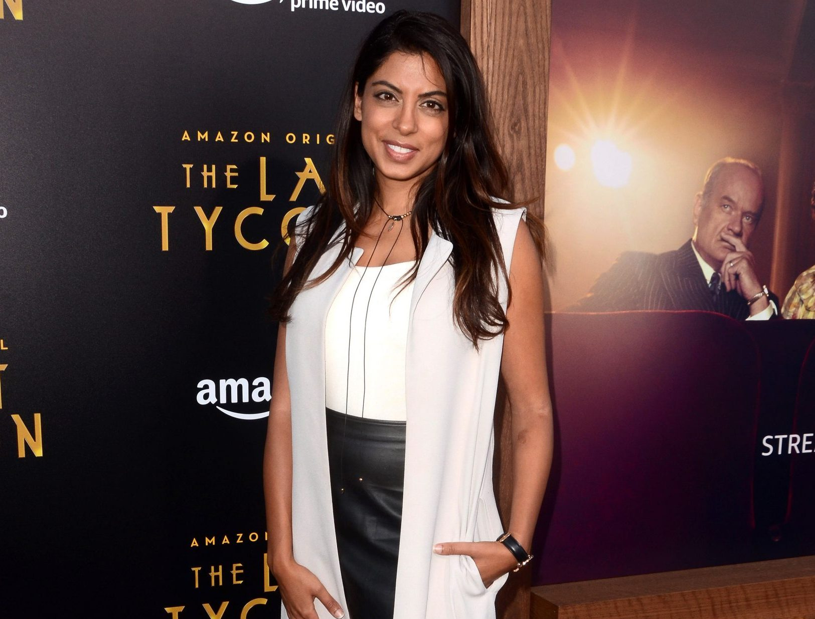 Aliya Jasmine smiles at a red carpet event. She has long, dark brown hair that sits over her shoulders. She wears a sleeveless white top with a light-coloured vest on top and a black skirt.