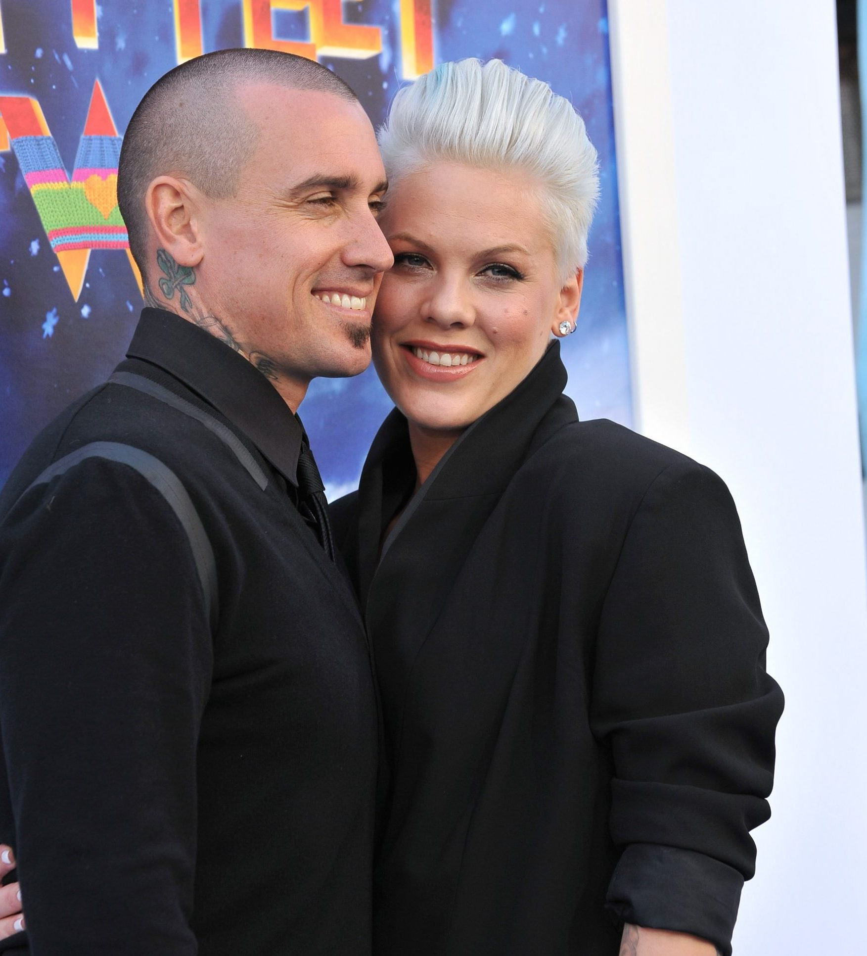 Carey Hart and Pink pose at a red carpet event. They stand close to each other and are both dressed in black, smiling.