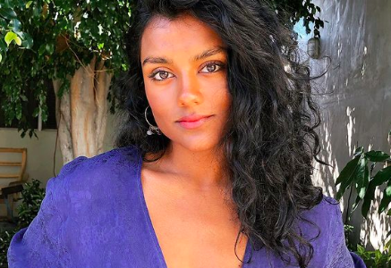 Simone Ashley poses in a garden. She has curly black hair, brown skin and wears a loose purple top that's tied in a knot below her chest.
