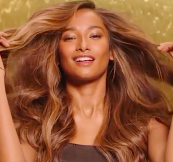 Nidhi Sunil in an excerpt from a video by L'Oreal paris. She has long brown hair and the background behind her is gold.