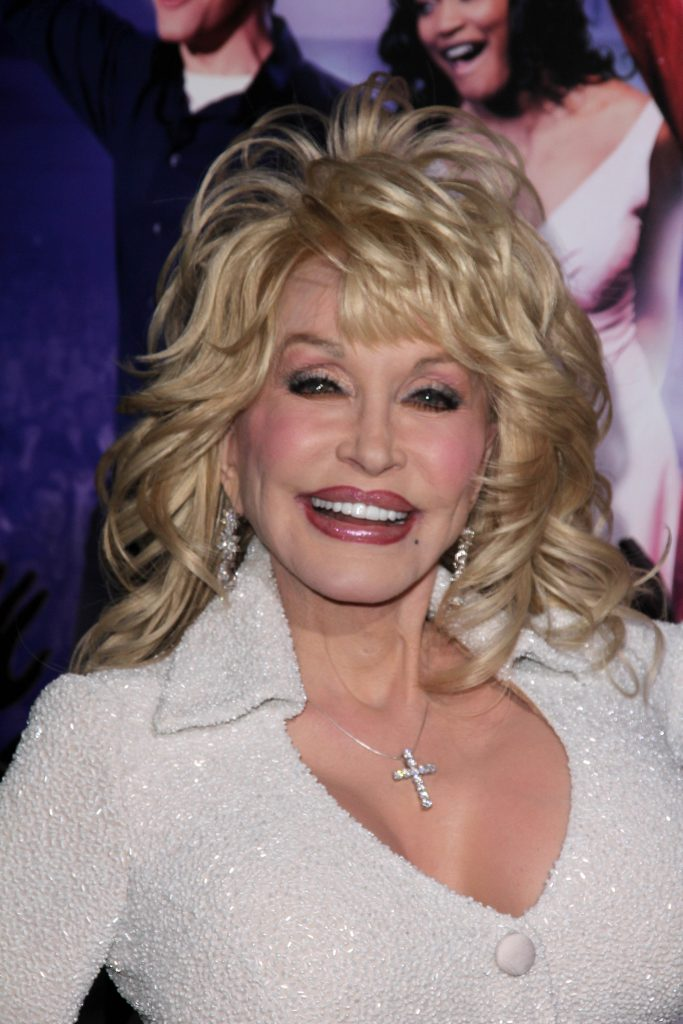 Dolly Parton smiling at a red carpet eveng with her signature big, blonde hair.