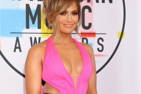 Jennifer Lopez smiles at a red carpet event. She wears a hot pink dress with a black waistband and has her hair in an elegant up-style.