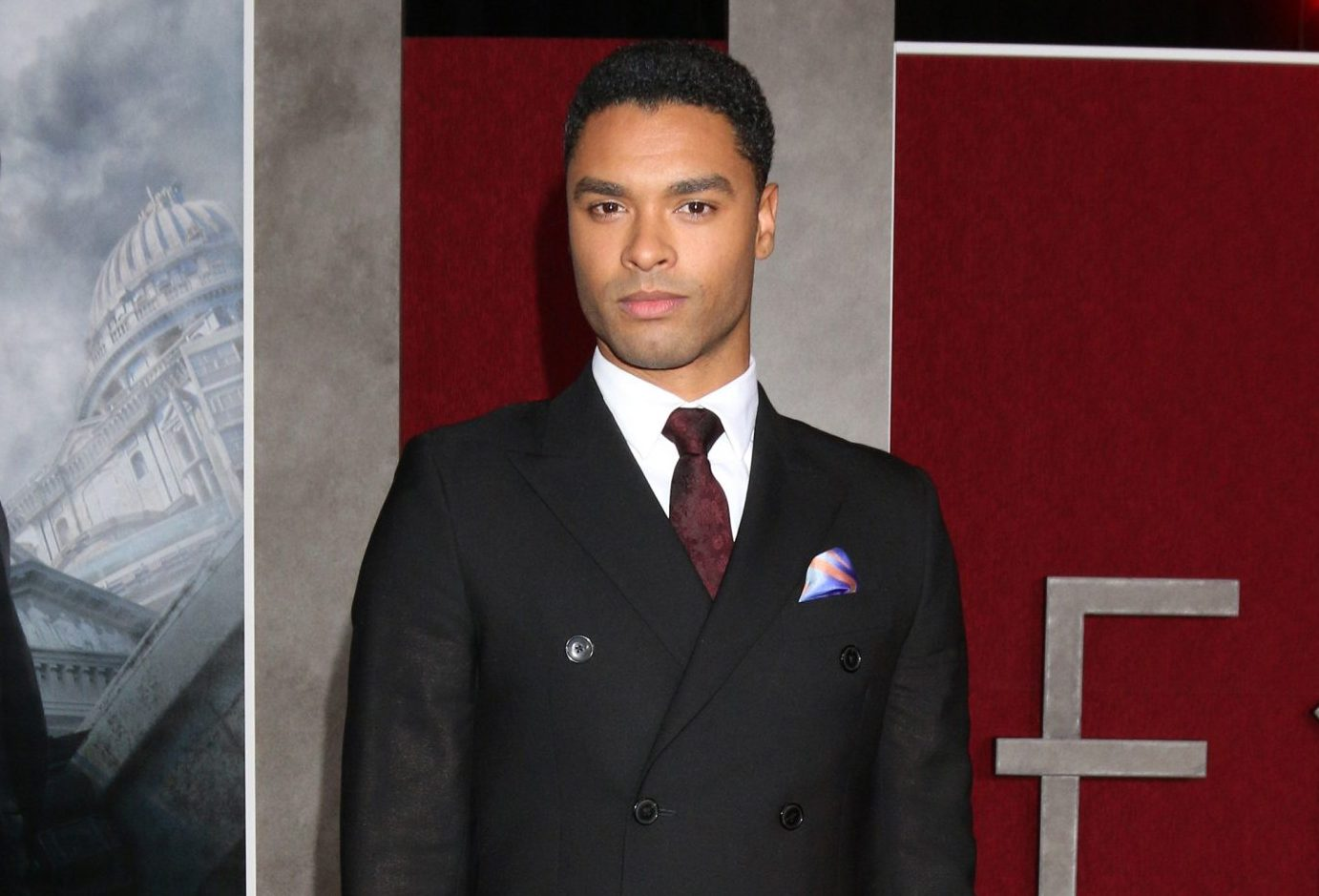 Regé-Jean Page attends a red carpet event. He is wearing a dark suit and deep red tie with a white shirt.