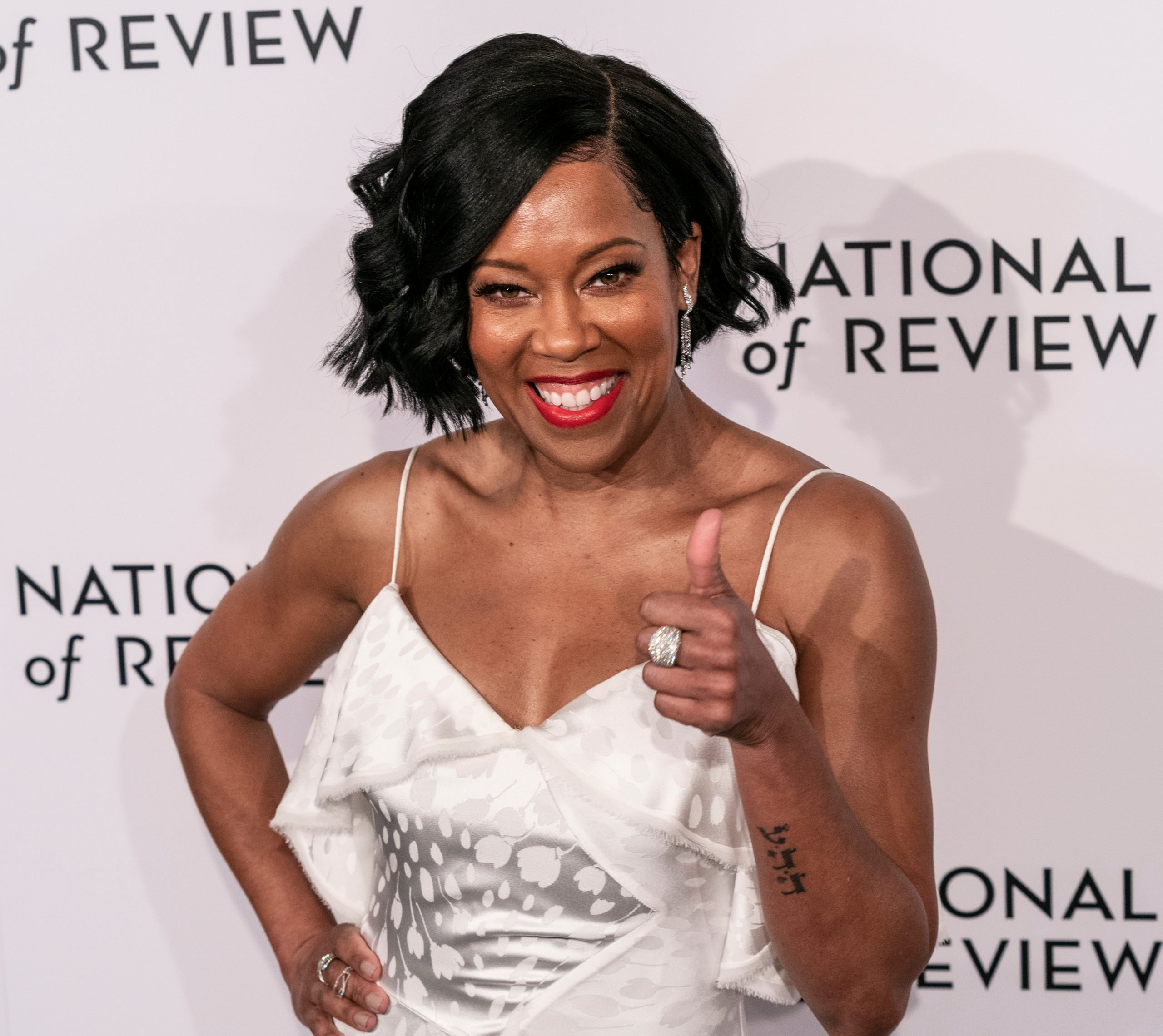 """Regina King smiles at a red carpet event and makes a """"thumbs up"""" gesture. She has black hair that sits in an elegant wavy bob and wears a white dress with thin straps."""