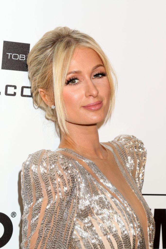 Paris Hilton smiles at a red carpet event. her blonde hair is tied back with some strands hanging around her face and she wears a sparkly, silver dress with shoulder pads.