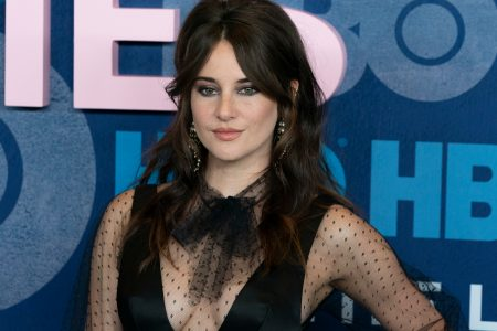 Shailene Woodley attends a red carpet event. She has dark brown hair and wears a black dress with see-through sleeves and a bow on her neck.