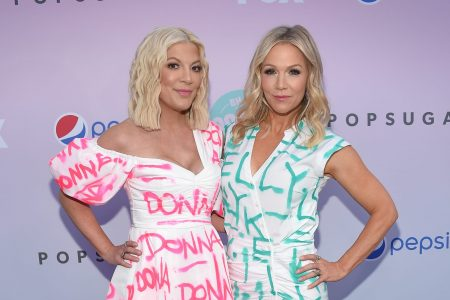 """Tori Spelling and Jennie Garth pose at a red carpet event. They both have wavy blonde hair that sits on their shoulders. Tori wears a white dress with """"Donna"""" written all over it in a pink, graffiti font. Jennie wears a white dress with """"Kelly"""" printed all over it in a graffiti font."""