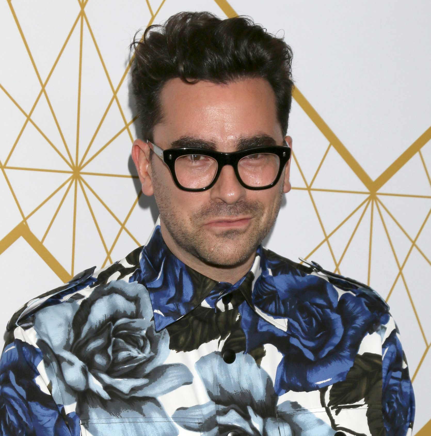 Dan Levy smiles at a red carpet event. He wears his signature thick framed black glasses and a floral blue and white shirt.