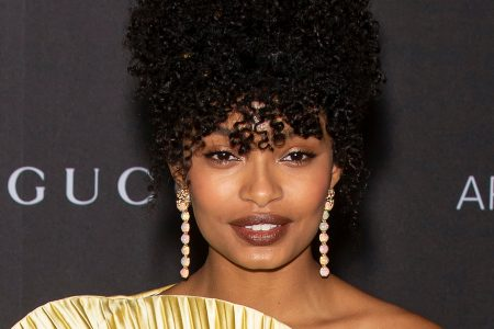 Yara Shahidi at a red crpet event. Her curly black hair sits atop her head. She wears a one shoulder gold dress with a pleated fan feature and dangly gold earrings.