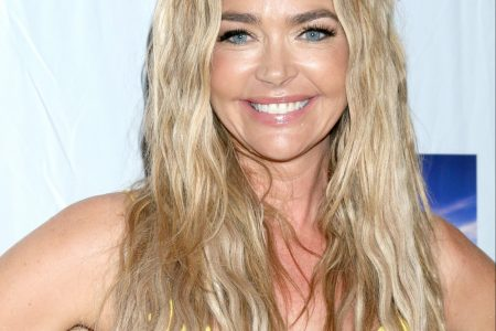 Denise Richards smiles at a red carpet event. She has long blonde wavy hair that sits past her shoulders and she's wearing a sleeveless yellow dress.