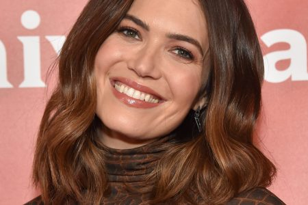 Mandy Moore tilts her head and smiles sweetly at a red carpet event. She has brown hair that sits on her shoulders and wears a brown turtle neck.