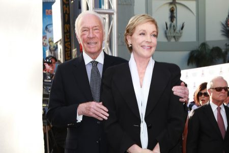 Christopher Plummer and Julie Andrews smile at a red carpet event. His arm is placed around her shoulder.