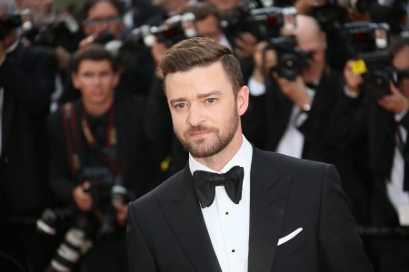 Justin Timberlake attends a red carpet event. He wears a black tuxedo, white shirt and a black bow tie. He is surrounded by paparazzi.