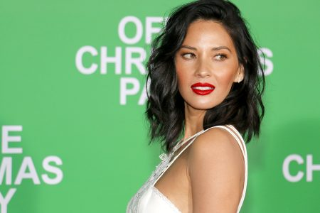 Olivia Munn looks over her shoulder at a red carpet event. She has dark brown hair that is dishevelled and sits above her shoulders. She wears a white sleeveless dress and bright red lipstick. The background is green.