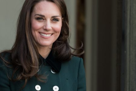 The Duchess of Cambridge smiles at a press event. She wears a double buttoned forest green coat and has dark brown hair that sits past her shoulders.