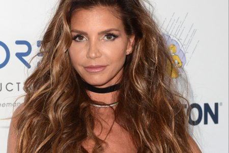 Charisma Carpenter attends a red carpet event. She has long brown wavy hair with some lighter streaks through it. She wears a black choker necklace and a sleeveless black dress.