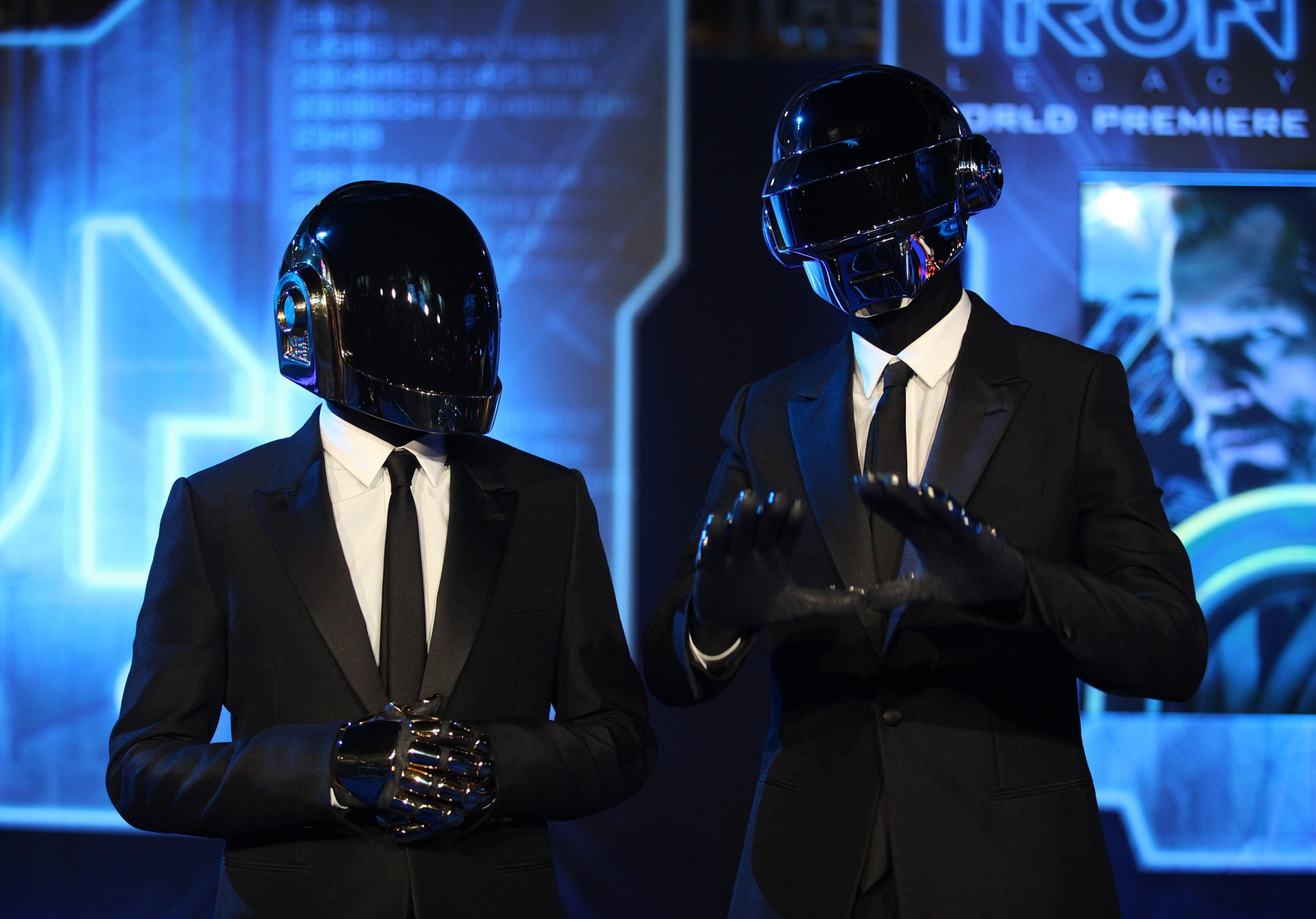 Daft Punk attend a red carpet event. They are wearing black suits and black helmets covering their faces. The background is an electronic blue with neon lights.