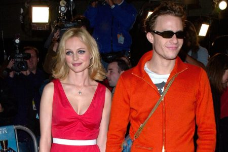 Heather Graham and Heath Ledger smile at a red carpet event. She wears a red dress and he wears a red coat with sunglasses. Behind them is a blur of paparazzi.