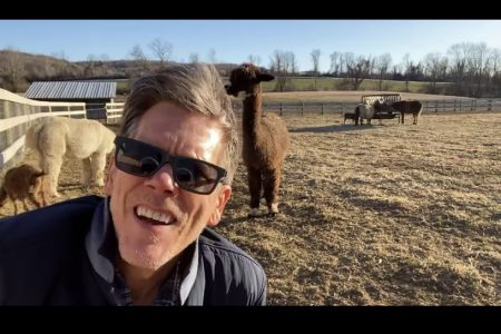 Kevin Bacon looks into the camera wearing sunglasses. He's out in a field with alcapas roaming behind him.