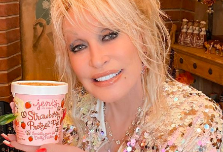 Dolly Parton smiles while holding a pink-coloured tub of her new ice cream.