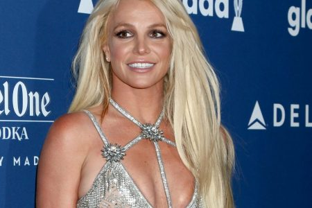Britney Spears smiles at a red carpet event. She has long blonde hair and wears a silver dress with a bikini style top.