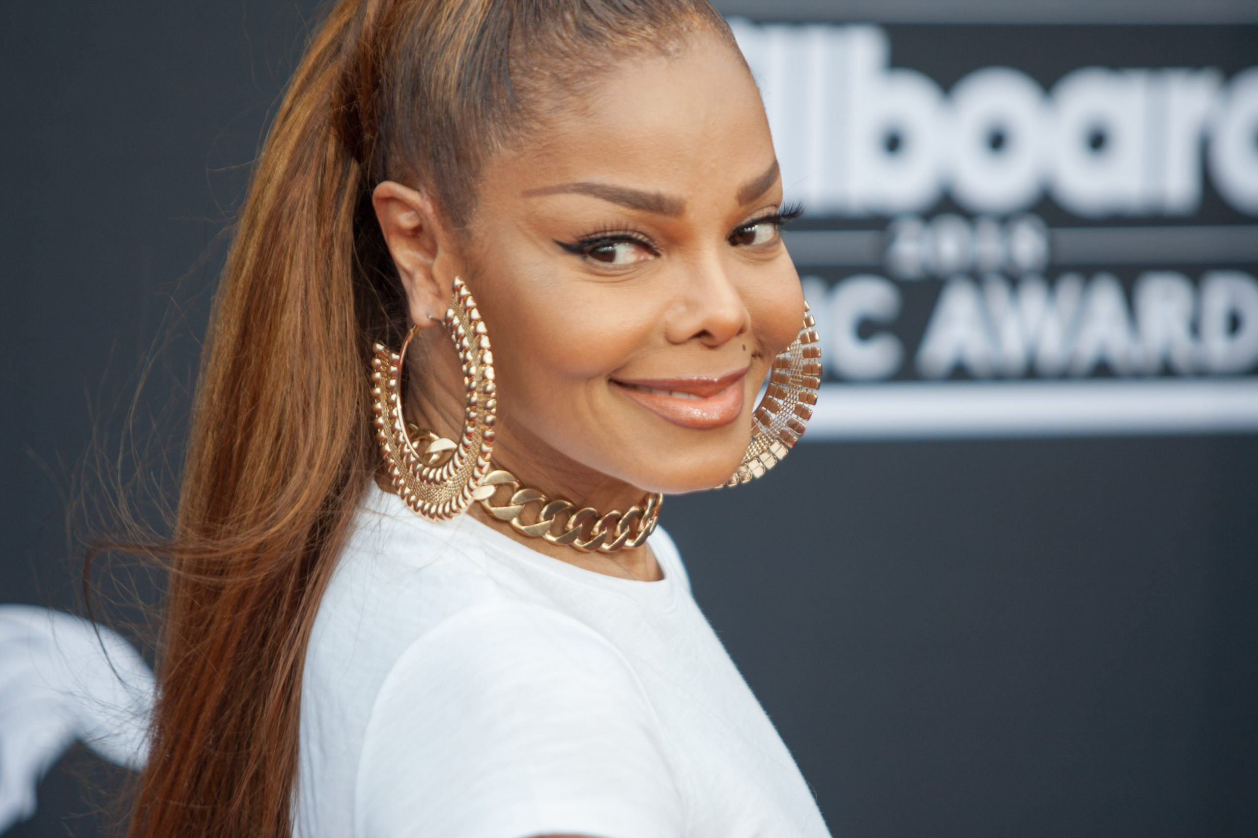 Janet Jackson smiles at a red carpet event. Her hair is tied back in a tight pony tail. She wears large, gold hoop earrings and a white top.