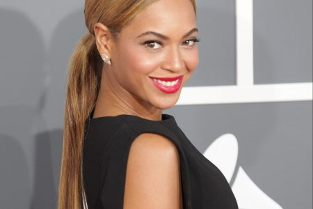 Beyonce smiles at a red carpet event. Her brown hair is tied back in a long ponytail. She has red lips and wears a black sleeveless dress.