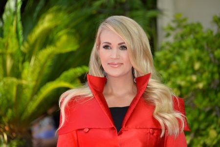 Carrie Underwood smiles at an outdoor press event. She has long blonde hair and wears a red jacket with a high collar.