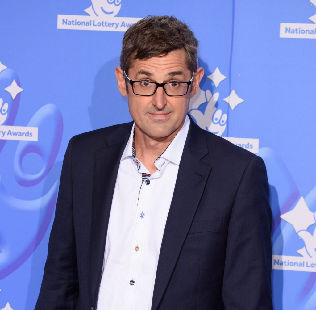 Louis Theroux attends a red carpet event wearing a white shirt and black suit jacket. He has his signature black glasses on.
