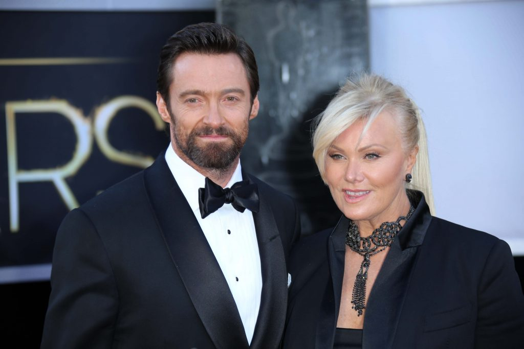 Hugh Jackman and Deborra-Lee Furness attend a red carpet event. He wears a tuxedo and has a short beard and moustache. Deborra-Lee wears a black jacket with a black necklace and her blonde hair is tied back. They are both smiling.