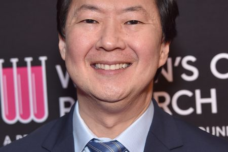 Ken Jeong smiles at a red carpet event. He has black hair and wears a blue suit and tie.