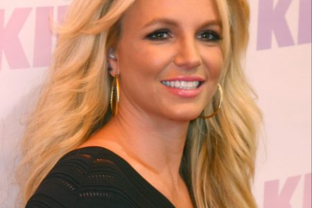 Britney Spears smiles at a red carpet event. She has long blonde layered hair and wears hoop earrings and a black top.