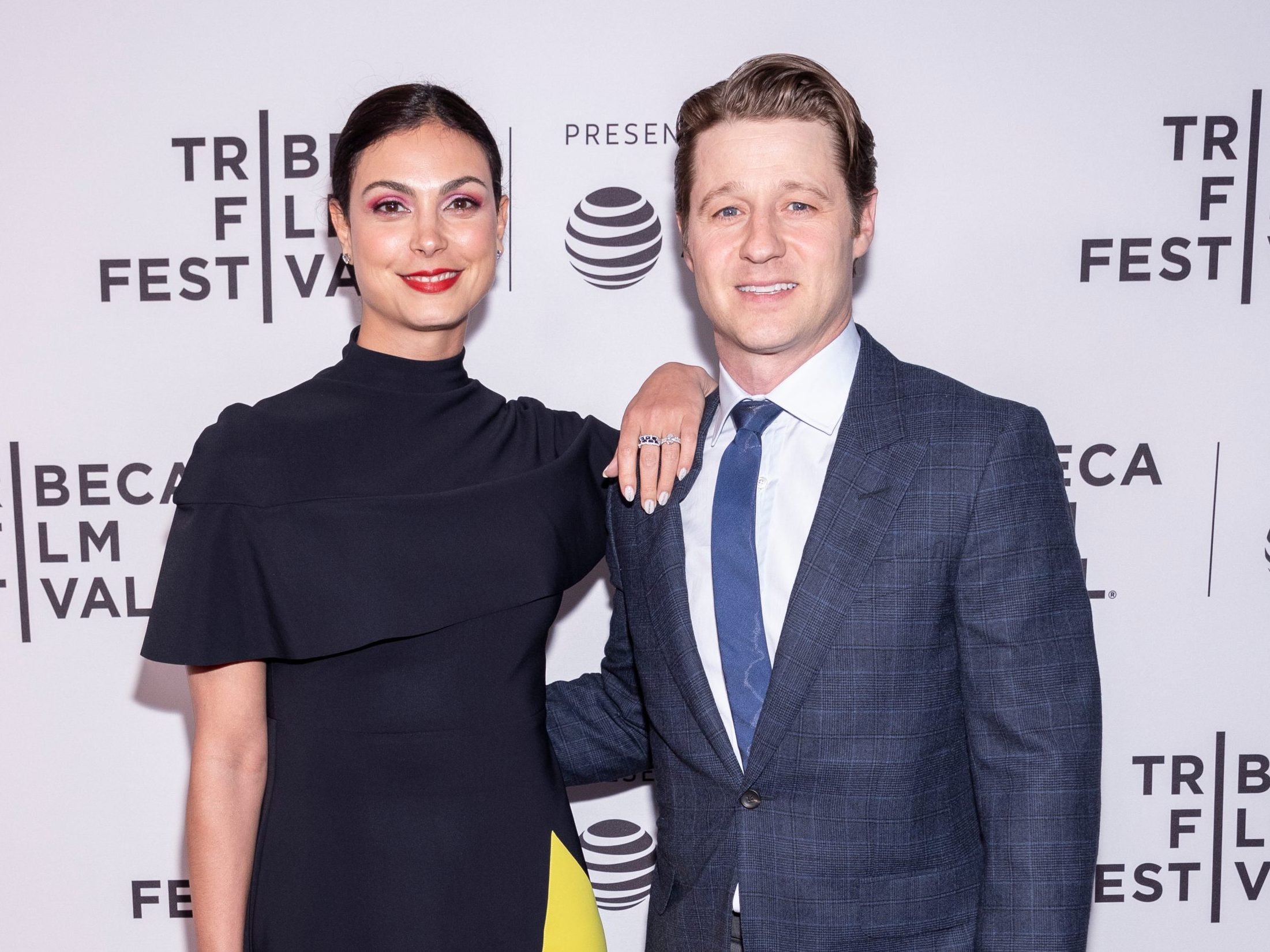 Morena Baccarin and Ben McKenzie smile at a red carpet event.