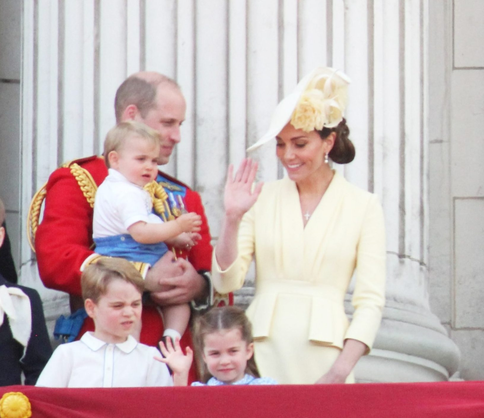Prince William, Duchess Catherine, Prince George, Princess Charlotte and Prince Louis wave from their balcony.