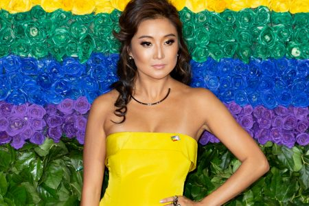 Ashley park wears a strapless yellow dress at a red carpet event. She has black hair that sits past her shoulders and the background is a colourful display of green, yellow, blue and purple floral arrangements.