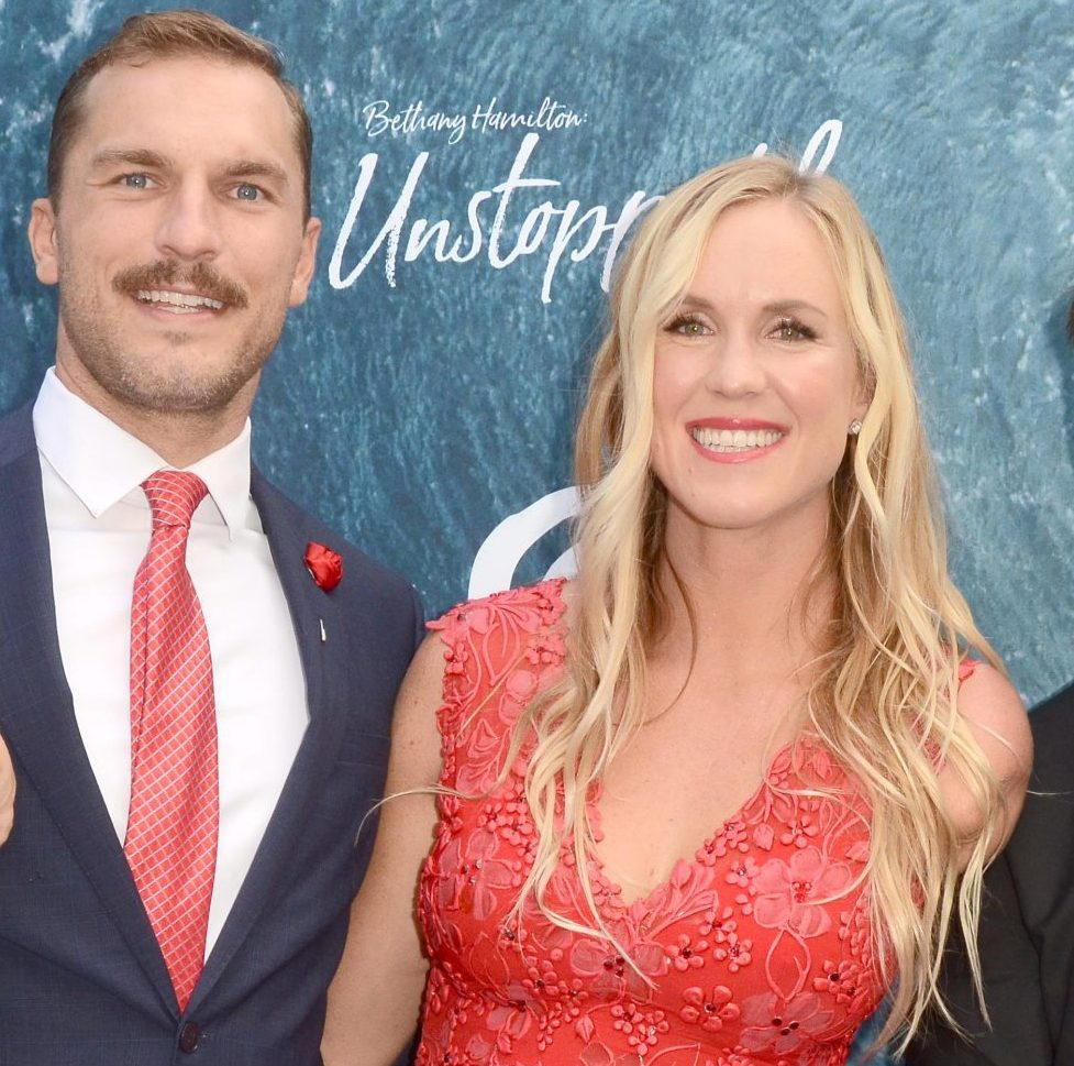 Adam Dirks and Bethany Hamilton smile at a red carpet event. He wears a dark suit and orange tie that matches Bethany's sleeveless dress. She has long wavy blonde hair.