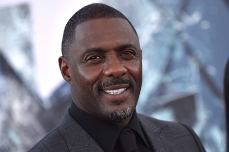 Idris Elba smiles at a red carpet event. He wears a black suit and shirt.