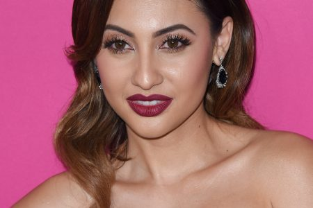 Francia Raisa at a red carpet event. She has brown hair that is elegantly styled over one shoulder and wears a strapless navy dress. Her makeup is striking with deep red lips.