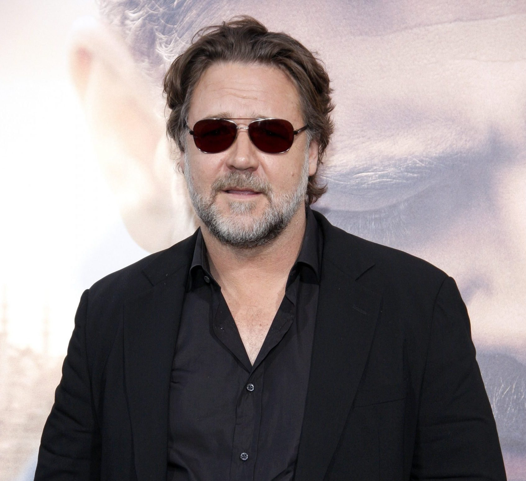 Russell Crowe attends a red carpet event wearing a black jacket, shirt and dark sunglasses.