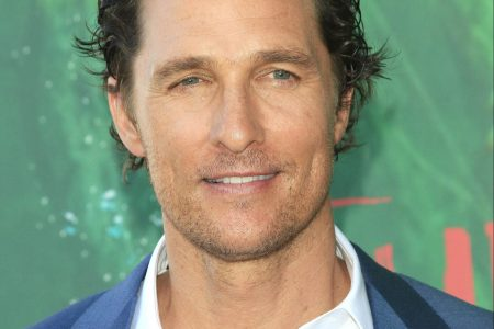 Matthew McConaughey smiles at a red carpet event. He wears a white shirt with a blue suit jacket. The background is green.