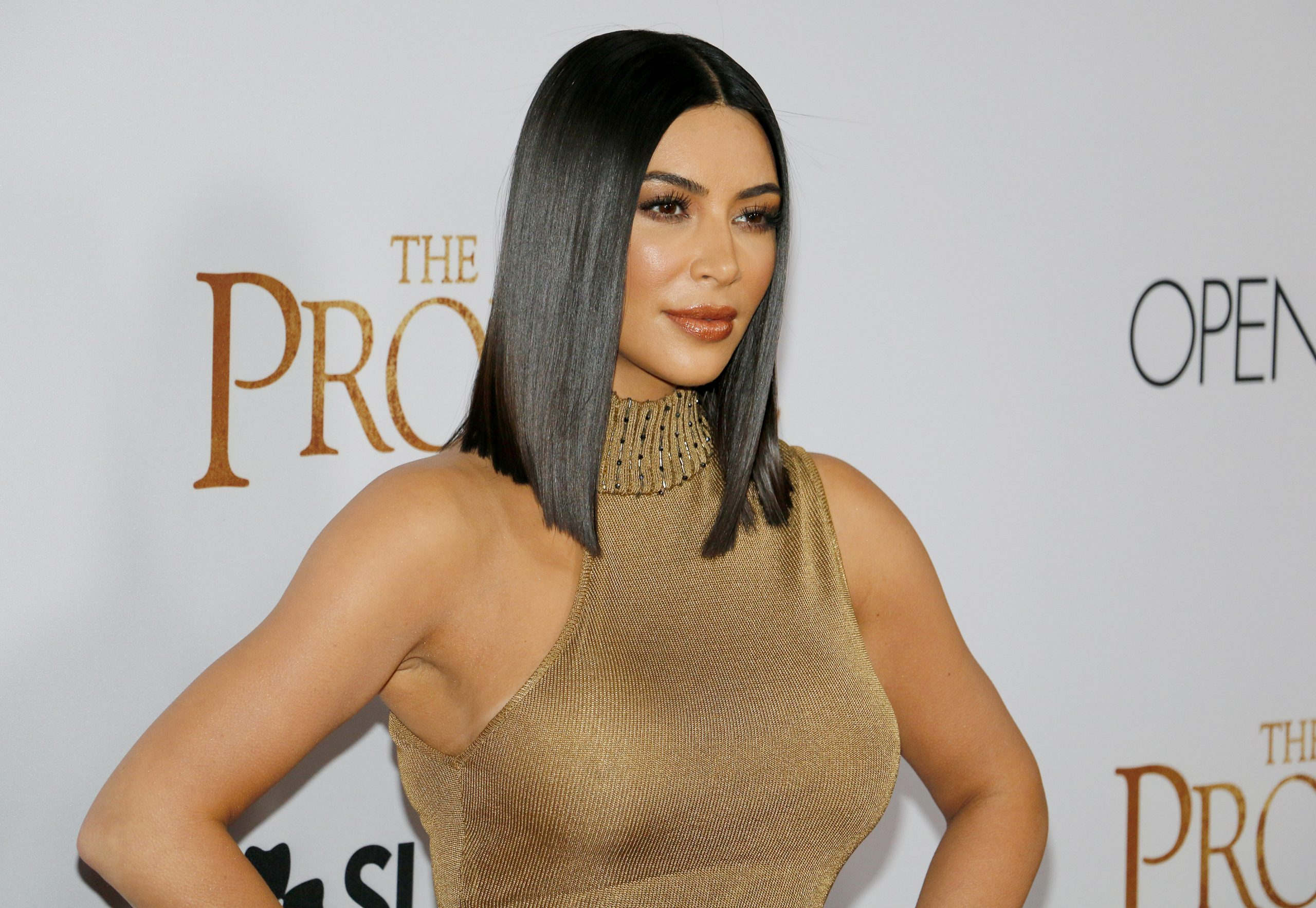 Kim Kardashian poses at a red carpet event. She has sleek black hair that sits on her shoulders and wears a high-neck gold, sleeveless dress.
