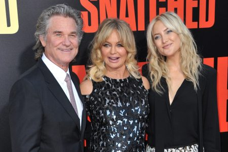 Kurt Russell, Goldie Hawn and Kate Hudson smile at a red carpet event.