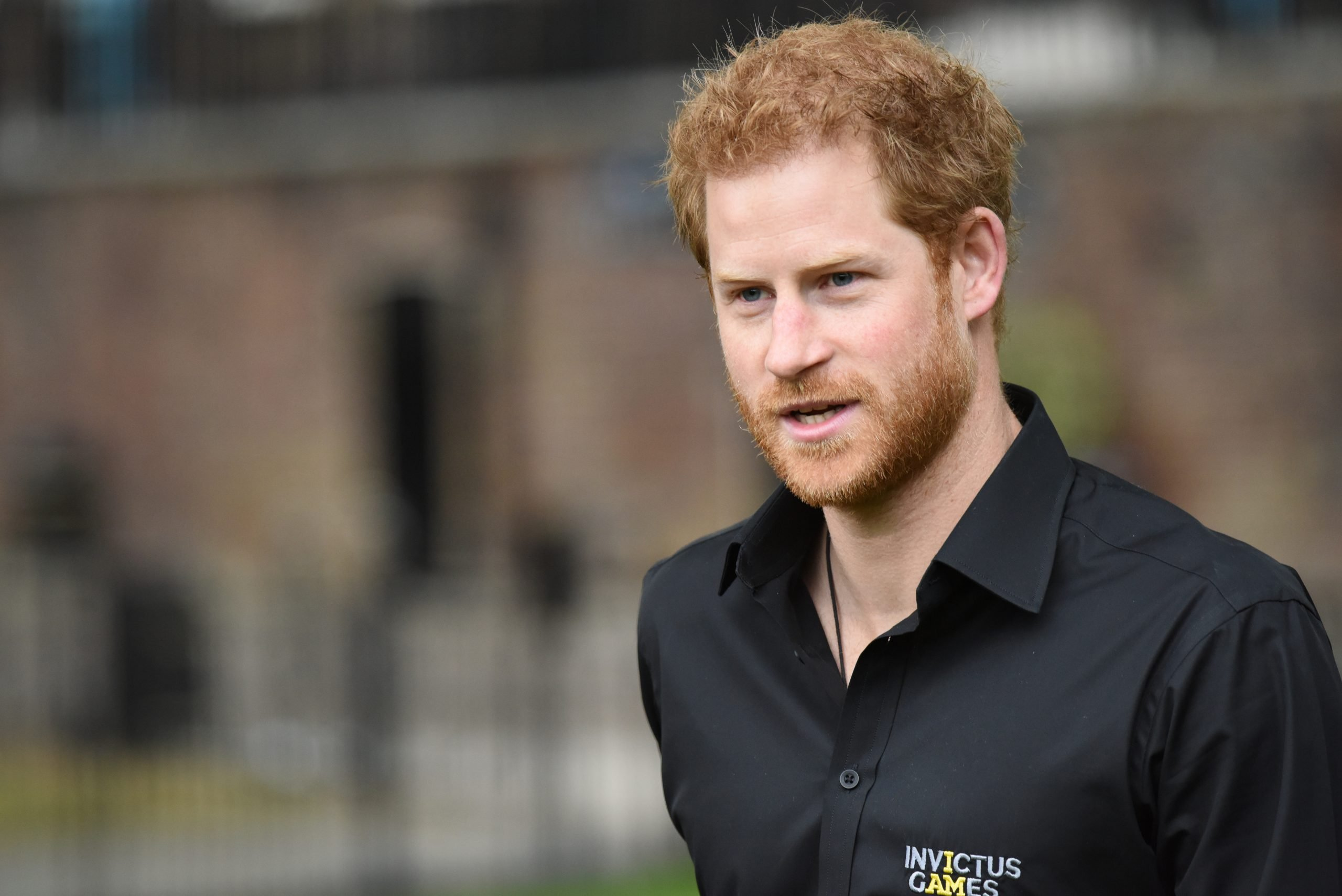 Prince Harry photographed at an outdoor press event. He wears a black shirt and is looking past the camera with his mouth partly open, mid sentence.