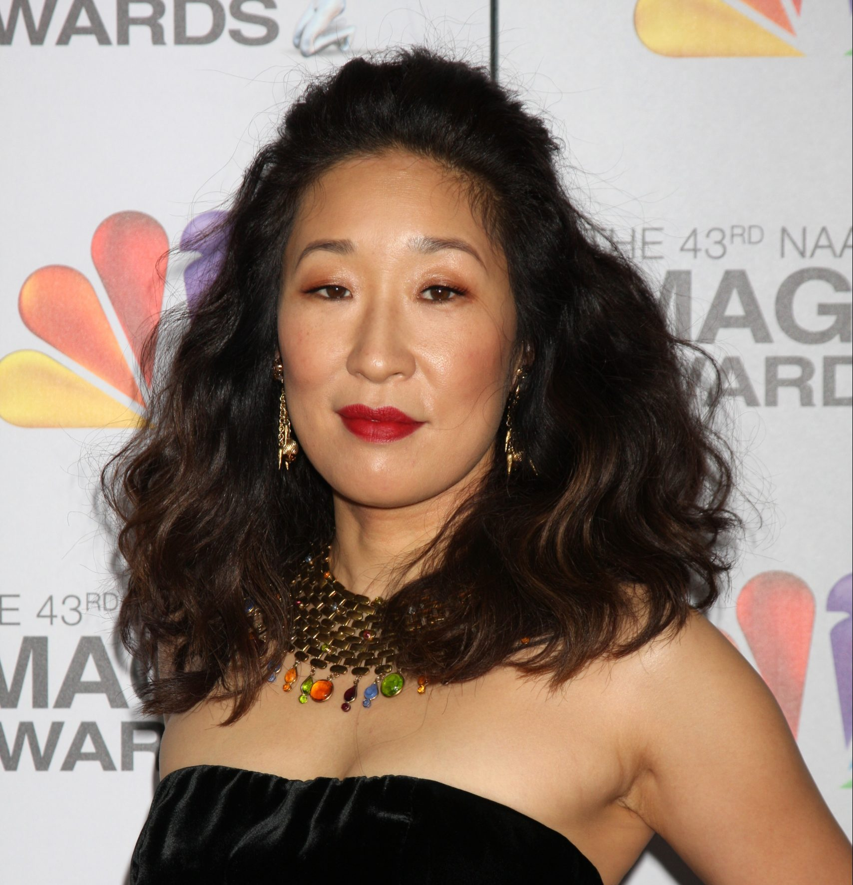 Sandra Oh smiles at a red carpet event. She wears a strapless black dress and a black necklace with colourful stones hanging off it.