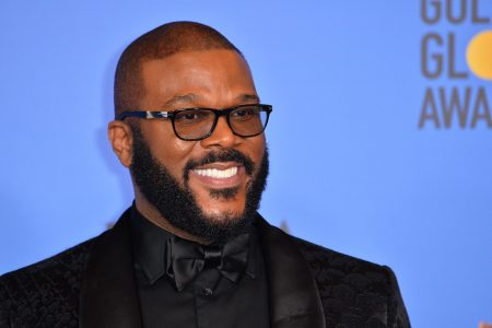 Tyler Perry smiles at a red carpet event. he has a short beard and moustache and wears tinted black glasses and a black tuxedo