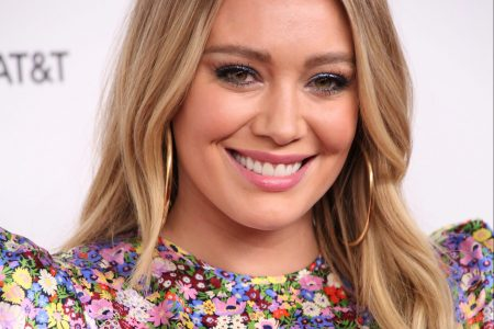 Hilary Duff smiles at a red carpet event wearing a shimmery floral dress.