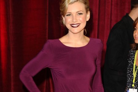 Saskia Hampele wears a deep burgundy dress at a red carpet event. She has one hand on her hip and her lipstick matches her dress.